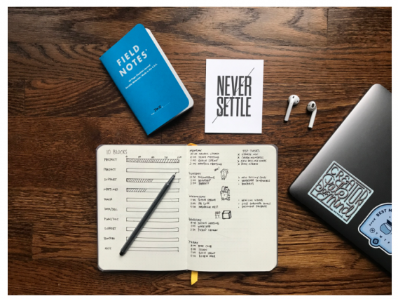 Top view of a desk with an open notebook, half a laptop that has stickers, airbuds, and a sticker that says never settle.